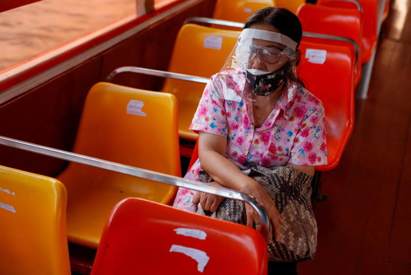 A woman wears a protective face mask while commuting by boat on the Chao Phraya river in Bangkok during the coronavirus disease (Covid-19) outbreak, on Wednesday. (Reuters photo)