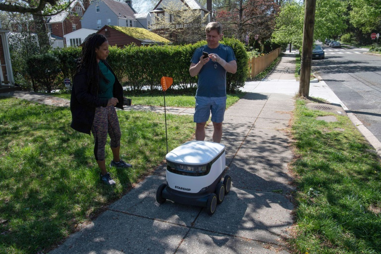 Kimmo Kartano uses his smartphone to open a food delivery robot from the Broad Branch Market grocery store as Audra Grant looks on in front of their house in the Chevy Chase neighbourhood of Washington.