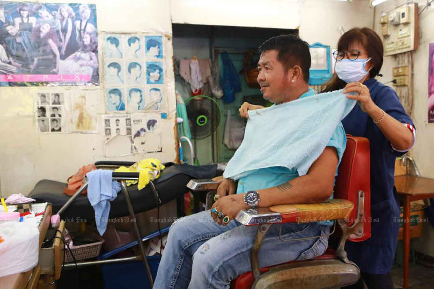 A hairdresser wears a face mask at a shop in Samut Prakan province last month, before the coronavirus shutdown. A decision will be made next week whether barber shops and some other businesses can reopen. (Photo: Somchai Poomlard)
