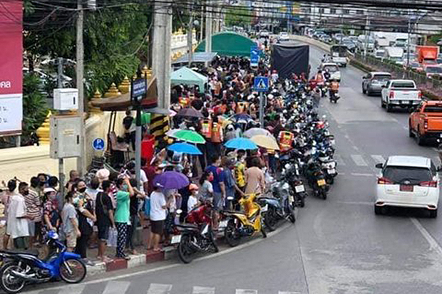 People crowd together in a long queue along Song Prapha Road to receive the free food being distributed by Wat Don Muang on Friday. (Photo from @LoveDO_DOO via @jorsor100radio Twitter accounts)