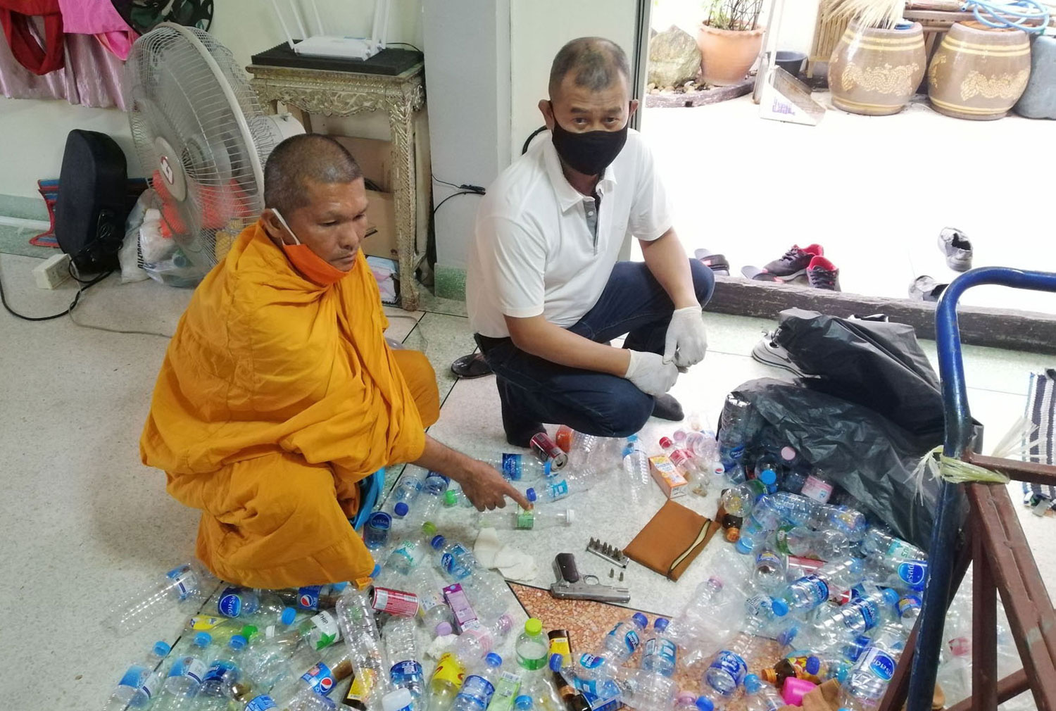 Phra Apiram Ruengthip, 46, a monk at Wat Mongkhol Nimit in Bang Sao Thong district of Samut Prakan, shows police the gun he hid in a bag plastic bag containing empty bottles following his arrest on charges of attempted murder of a layman living at the same temple. (Photo by Sutthiwit Chayutworakan)