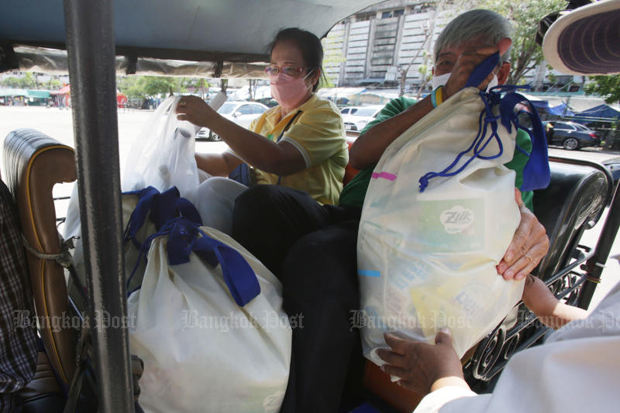 People affected by the coronavirus outbreak receive handouts from the Social Development and Human Security Ministry in Huay Kwang district of Bangkok on Sunday. (Photo by Apichit Jinakul)