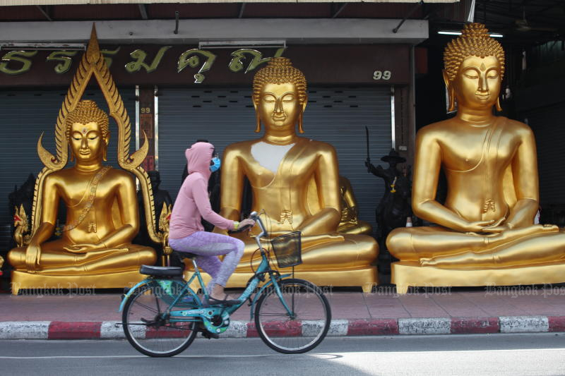A woman pedals past a shop on Siriphong Road near the Giant Swing on Sunday. (Photo by Apichart Jinakul)