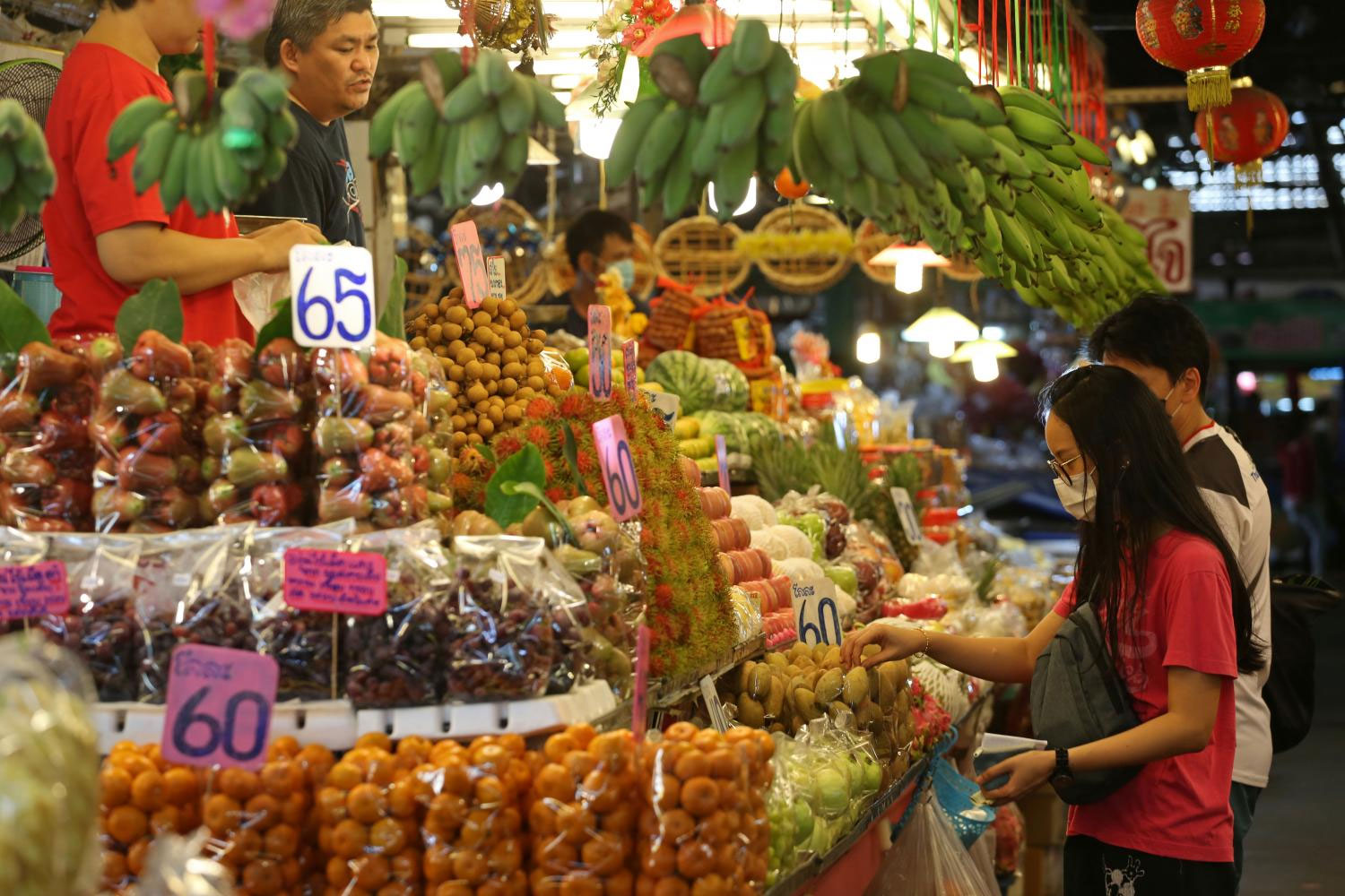 Shoppers wear masks while browsing produce at a grocery stall in Min Buri. (Photo by Varuth Hirunyatheb)