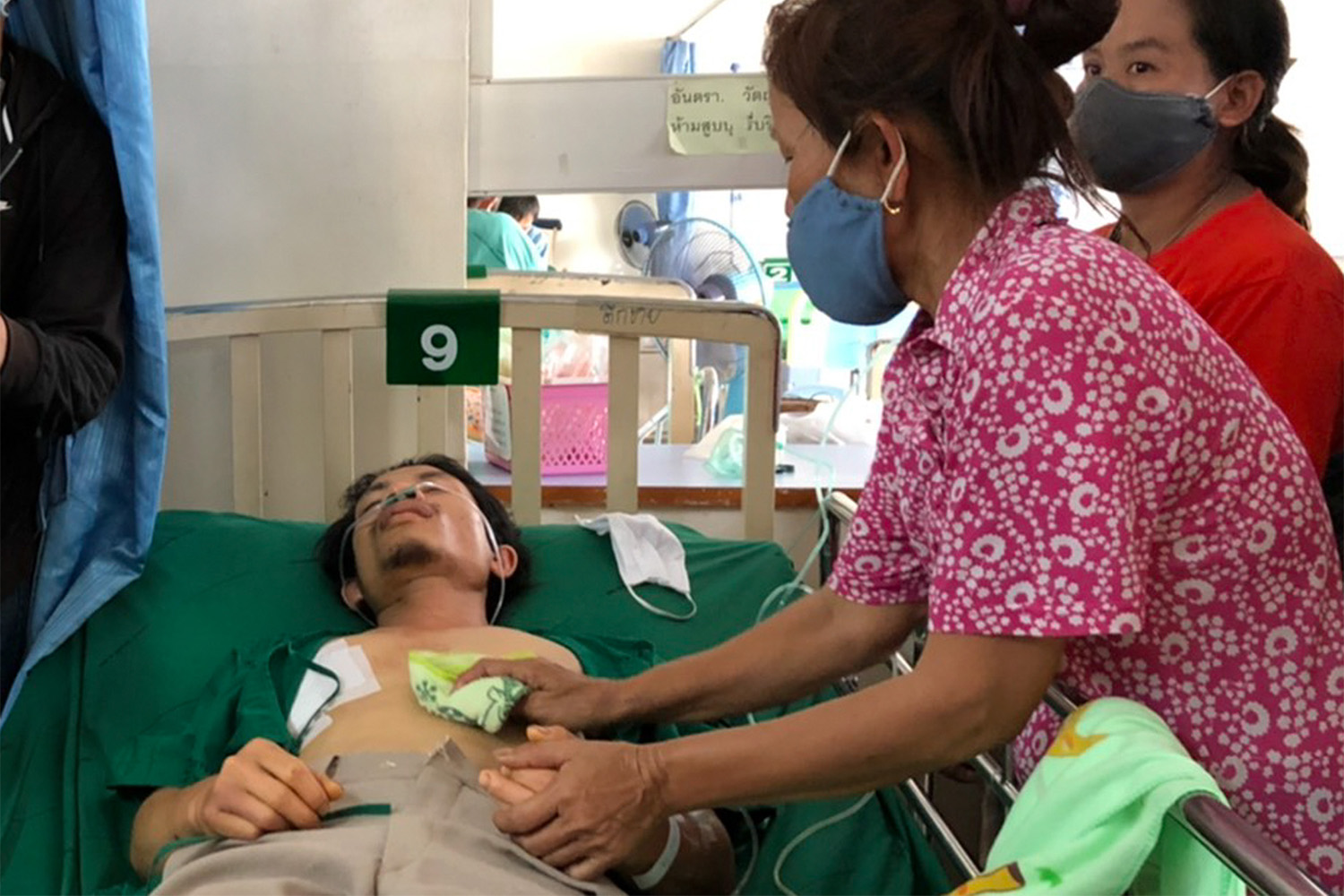 Severely injured Yutthana Saisa is treated at That Phanom Crown Prince Hosital in That Phanom district of Nakhon Phanom, with his mother at his side on Sunday. (Photo: Pattanapong Sripiachai)