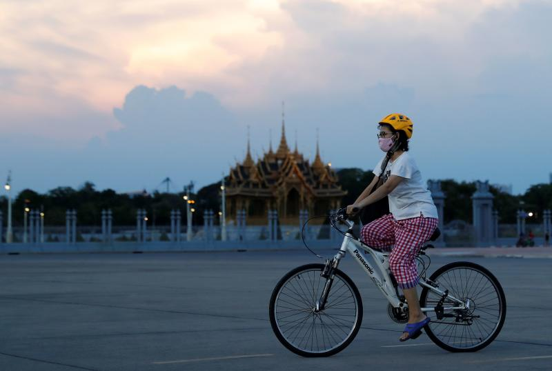 A woman wearing a protective mask rides a bike during the outbreak of the coronavirus disease (Covid-19) in Bangkok on Sunday. (Reuters photo)