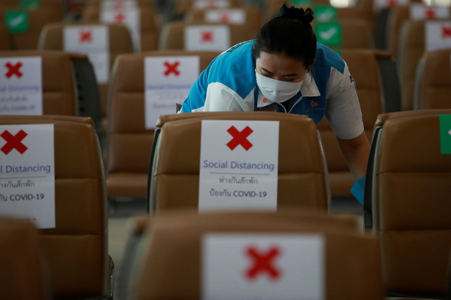A staff wearing a protective face mask cleans empty seats at the Suvarnabhumi Airport in Samut Prakan province on Thursday. (Reuters photo)