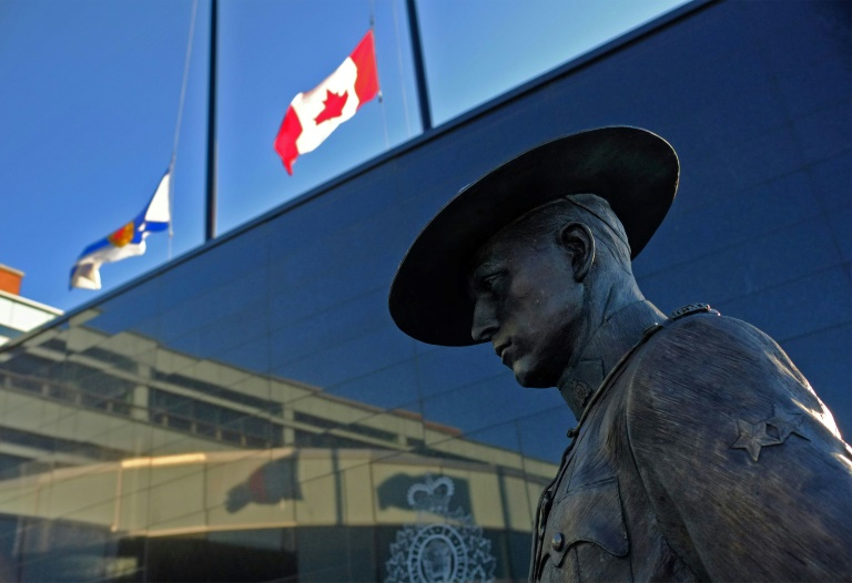 Flags of Nova Scotia and Canada fly at half-staff outside the Nova Scotia Royal Canadian Mounted Police headquarters in Dartmouth, Nova Scotia, after at least 10 people including an RCMP officer were killed in a shooting rampage.