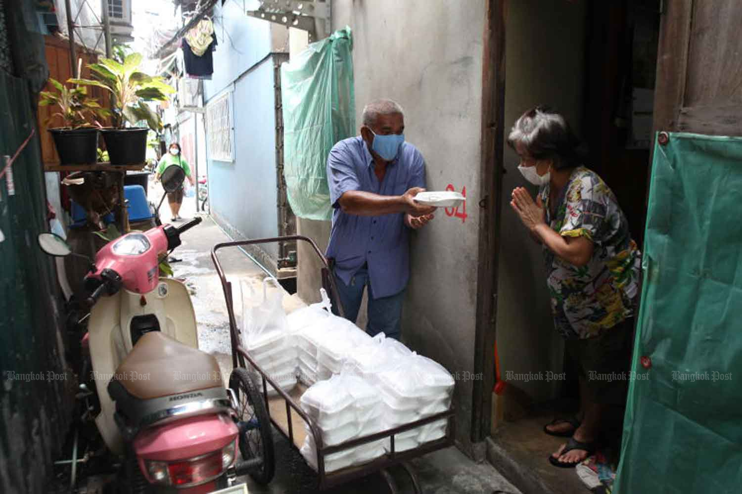 A community leader in Klong Toey district hands out a lunch box to a local resident. The food-sharing project, funded by Muang Thai Insurance Plc, is aimed at helping vulnerable individuals affected by the Covid-19 pandemic. Arnun Chonmahatrakool