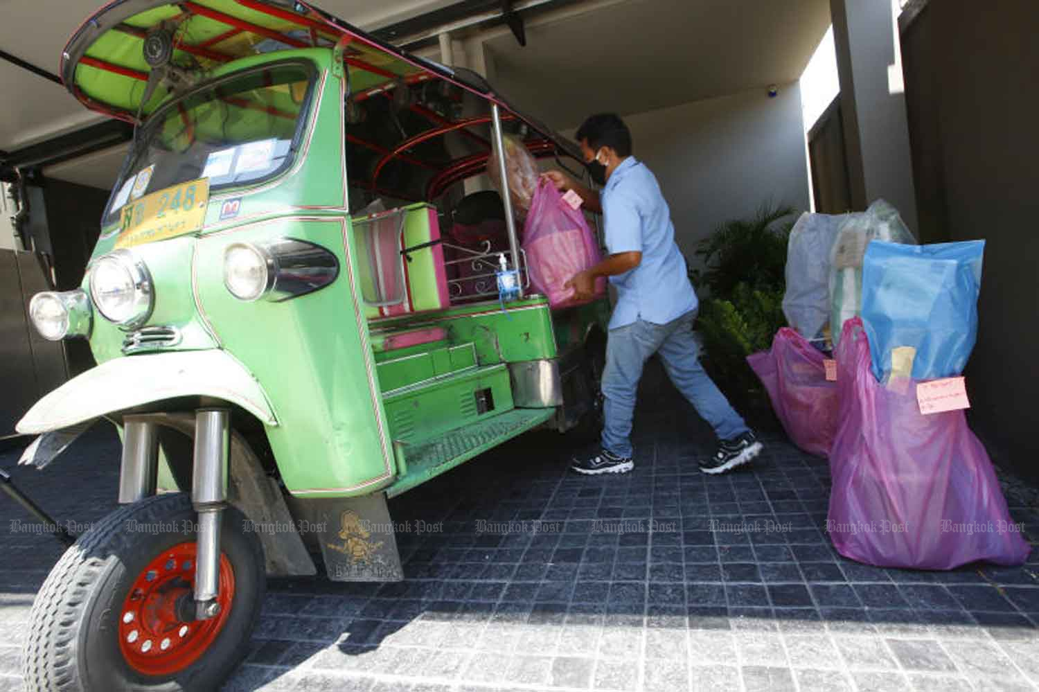 A tuk-tuk driver places goods in his vehicle for a delivery service which has replaced his old job, following a sharp drop in passenger numbers during the spread of Covid-19. Pornprom Satrabhaya