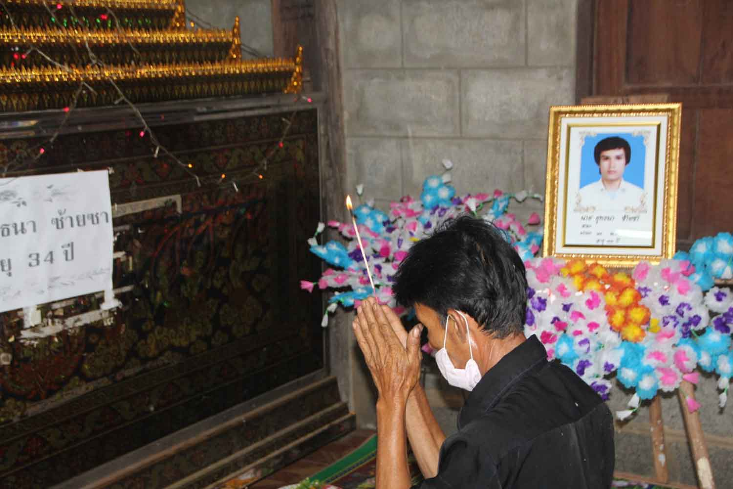 Niwat Saisa pays tribute to his son Yutthana, who died with severe injuries while in military custody in Nakhon Phanom province.(Photo: Pattanapong Sripiachai)