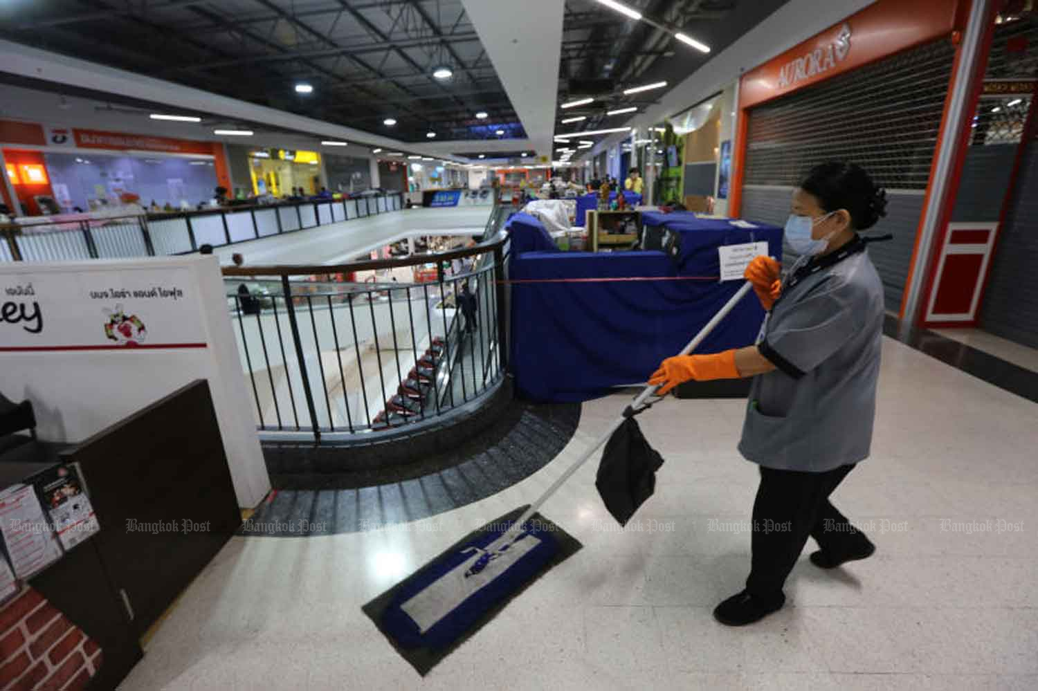 A cleaner works at a shopping centre in Samut Prakan province on Monday. All shops in the mall except for the grocery section were closed to curb Covid-19. (Photo: Wichan Charoenkiatpakul)