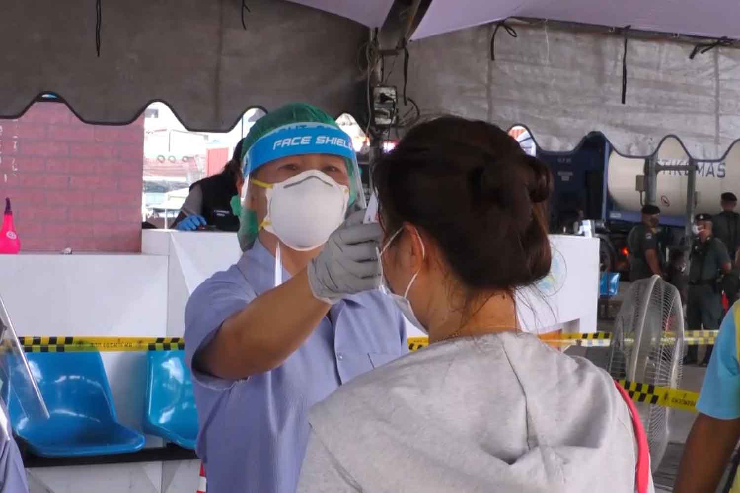 A Thai returnee from Malaysia has her temperature taken at the Sadao immigration checkpoint in Songkhla province. (Photo: Assawin Pakkawan)