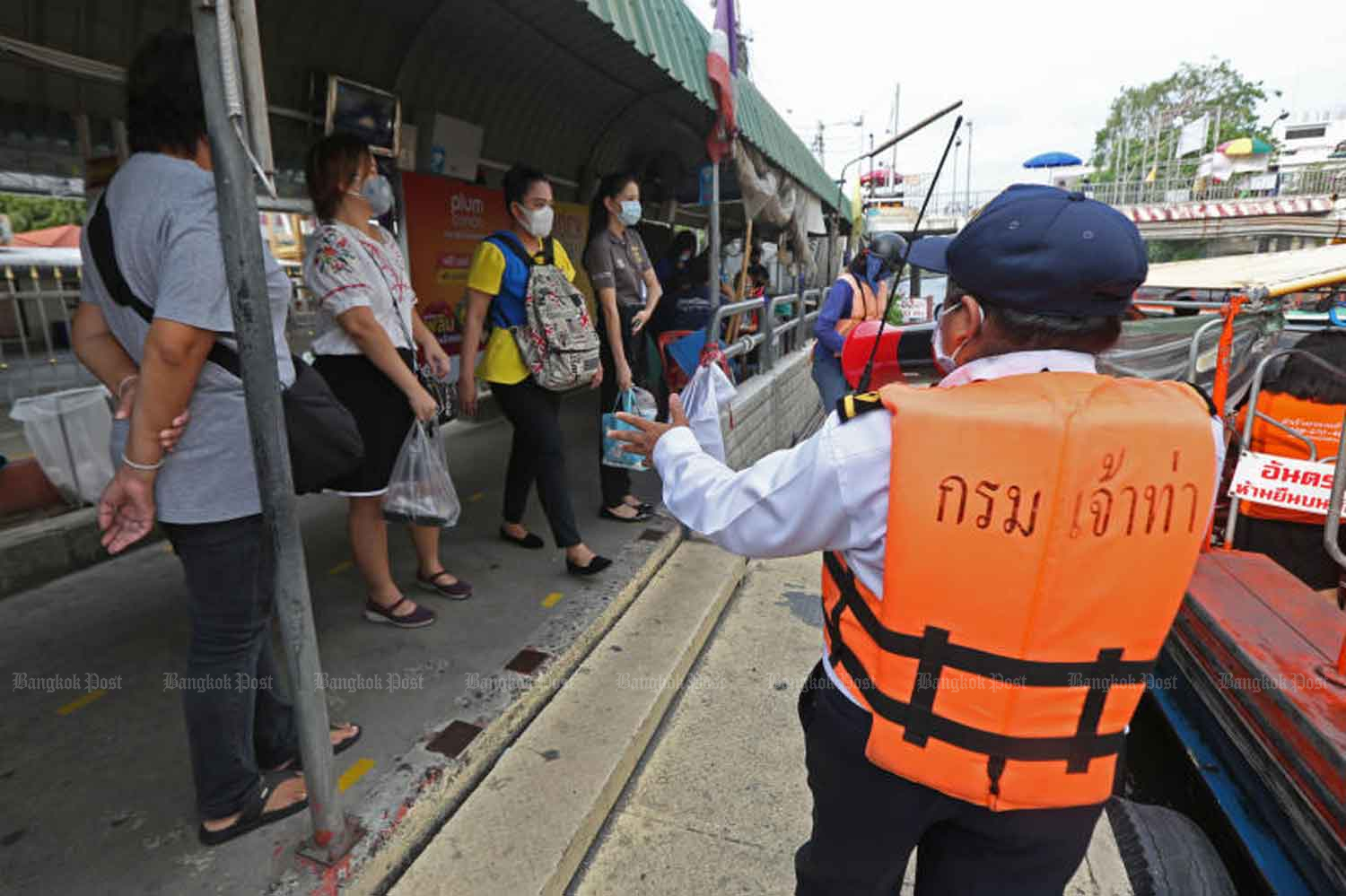 An official tells commuters to keep their distance from each other at the passenger boat pier in Bang Kapi district of Bangkok on Wednesday, when the government reported only 15 new cases of Covid-19 infection. Varuth Hirunyatheb