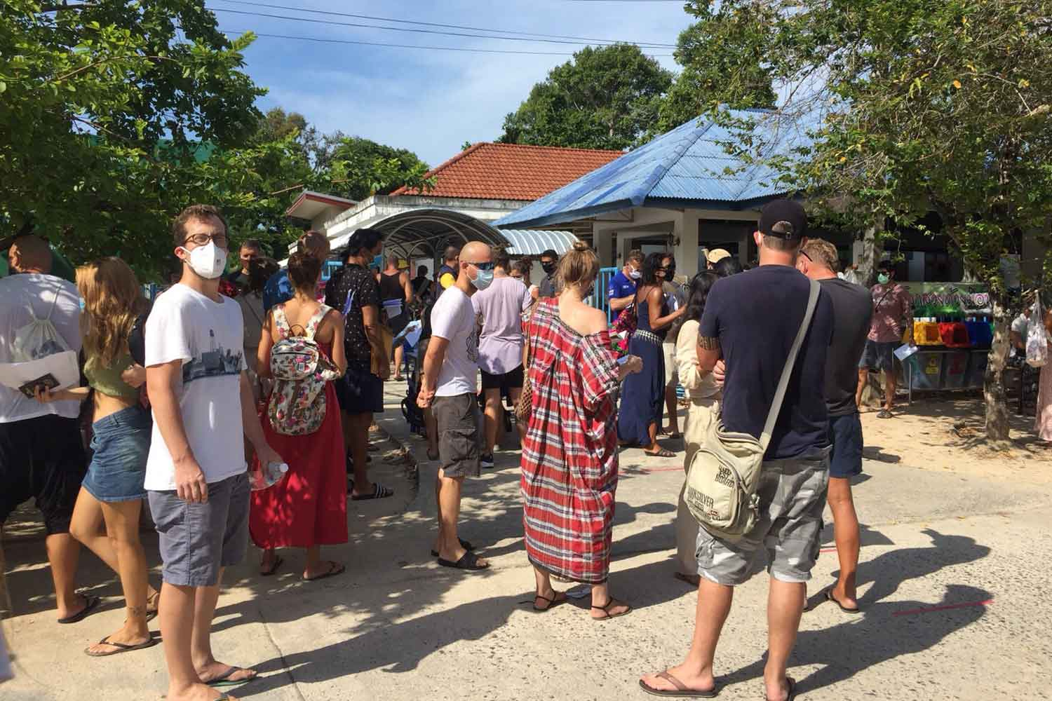 Tourists have their visas extended at a mobile unit of immigration police on Koh Samui, Surat Thani. (Photo: Supapong Chaolan)