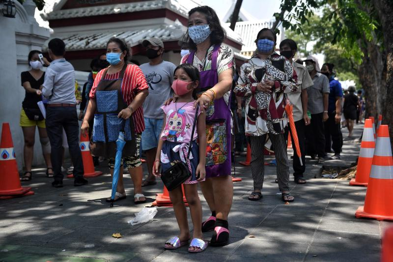 Families affected by unemployment following lockdown measures to halt the spread of the Covid-19 coronavirus line up for food donations at Wat Bowonniwetwiharn in Bangkok on Wednesday. (AFP photo)
