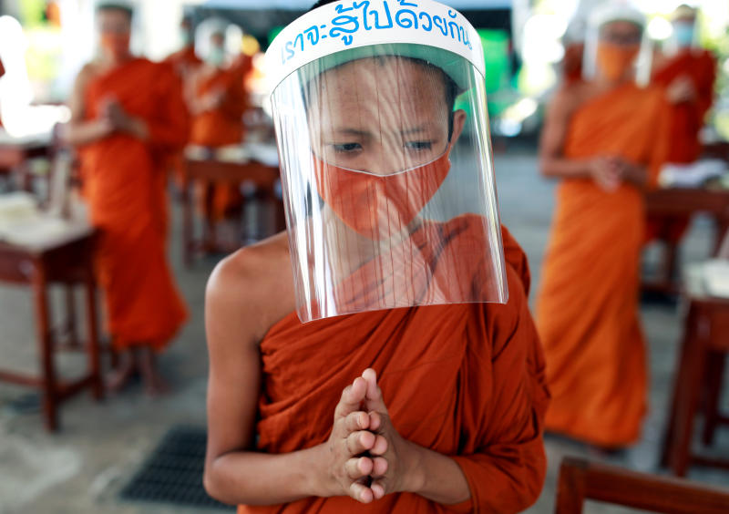 Novice monks wearing face shields and protective face masks attend a lesson at Wat Molilokayaram monastic educational institute during the coronavirus disease outbreak in Bangkok on Wednesday.
