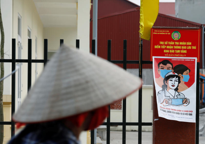 A farmer rides a bycycle past a poster warning about the coronavirus disease outbreak in Hanoi on Wednesday. (Reuters photo)