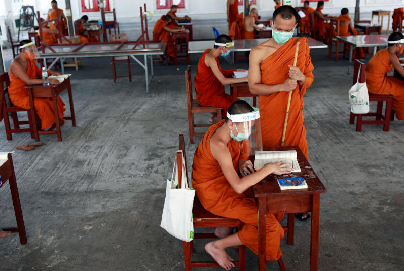 Novice monks wearing face shields and protective face masks attend a lesson at Wat Molilokayaram monastic educational institute in Bangkok on Wednesday. (Reuters photo)