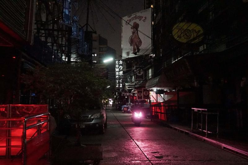 This photo taken on April 4, 2020 shows a motorbike passing through the closed down Soi Cowboy street in Bangkok, a road usually busy with sex workers and customers but now closed for business as authorities seek to halt the spread of the Covid-19 coronavirus. (AFP file photo)