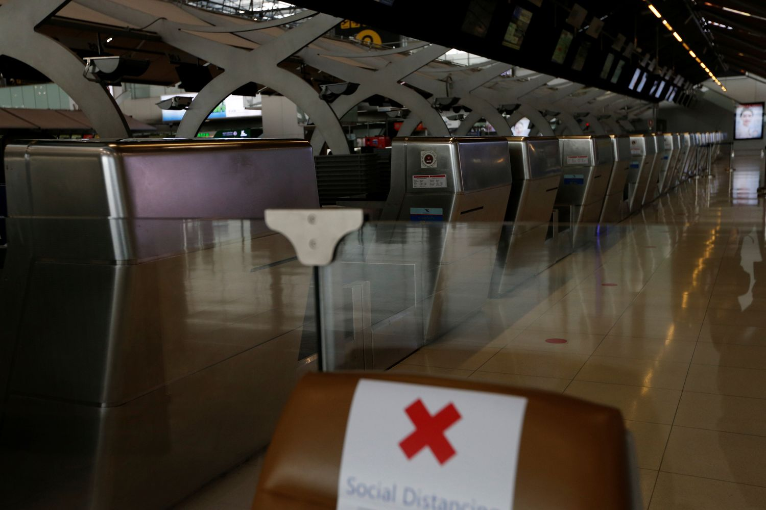 Empty check-in counters are seen at Suvarnabhumi airport on April 16 as the government extended a ban on incoming passenger flights until the end of the month. (Reuters photo)