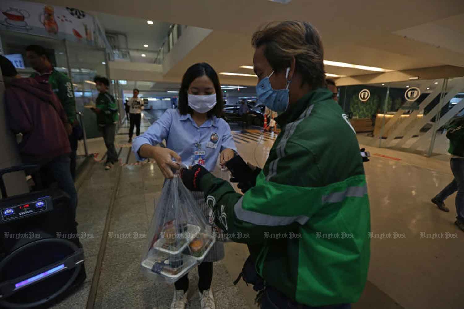 A delivery man is receiving food in plastic bag and boxes from a vendor at a shopping centre in Bangkok as dining is banned at restaurants due to the coronavirus disease pandemic. (Photo by Varuth Hirunyatheb)