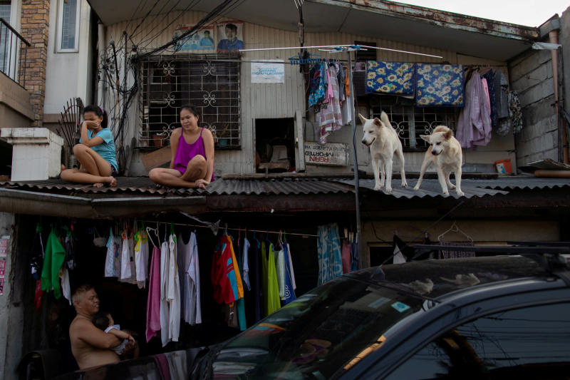 Girls hang out with their dogs on the roof of their house as the Philippine government enforces home quarantine to contain the coronavirus disease outbreak in Metro Manila on Tuesday. (Reuters photo)