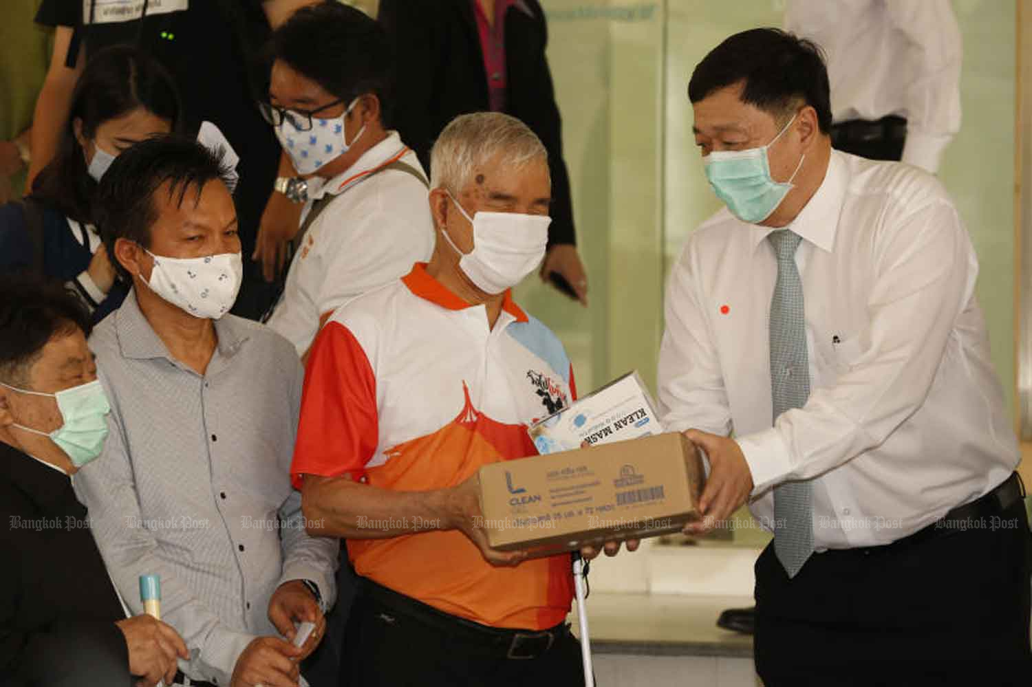 Representatives of Disabilities Thailand submit their written request for special financial assistance for people with disabilities during the Covid-19 crisis to Prasong Poontaneat, right, permanent secretary for finance, at the Finance Ministry in Bangkok on Friday. (Photo: Pornprom Satrabhaya)