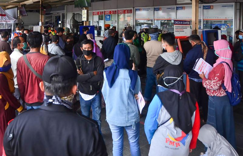 Indonesians line up in front of a bus station ticket box to get refund for their purchased tickets in Bekasi, West Java, on Thursday after the government announced the ban on returning home amid concern to the spread of coronavirus. (AFP photo)