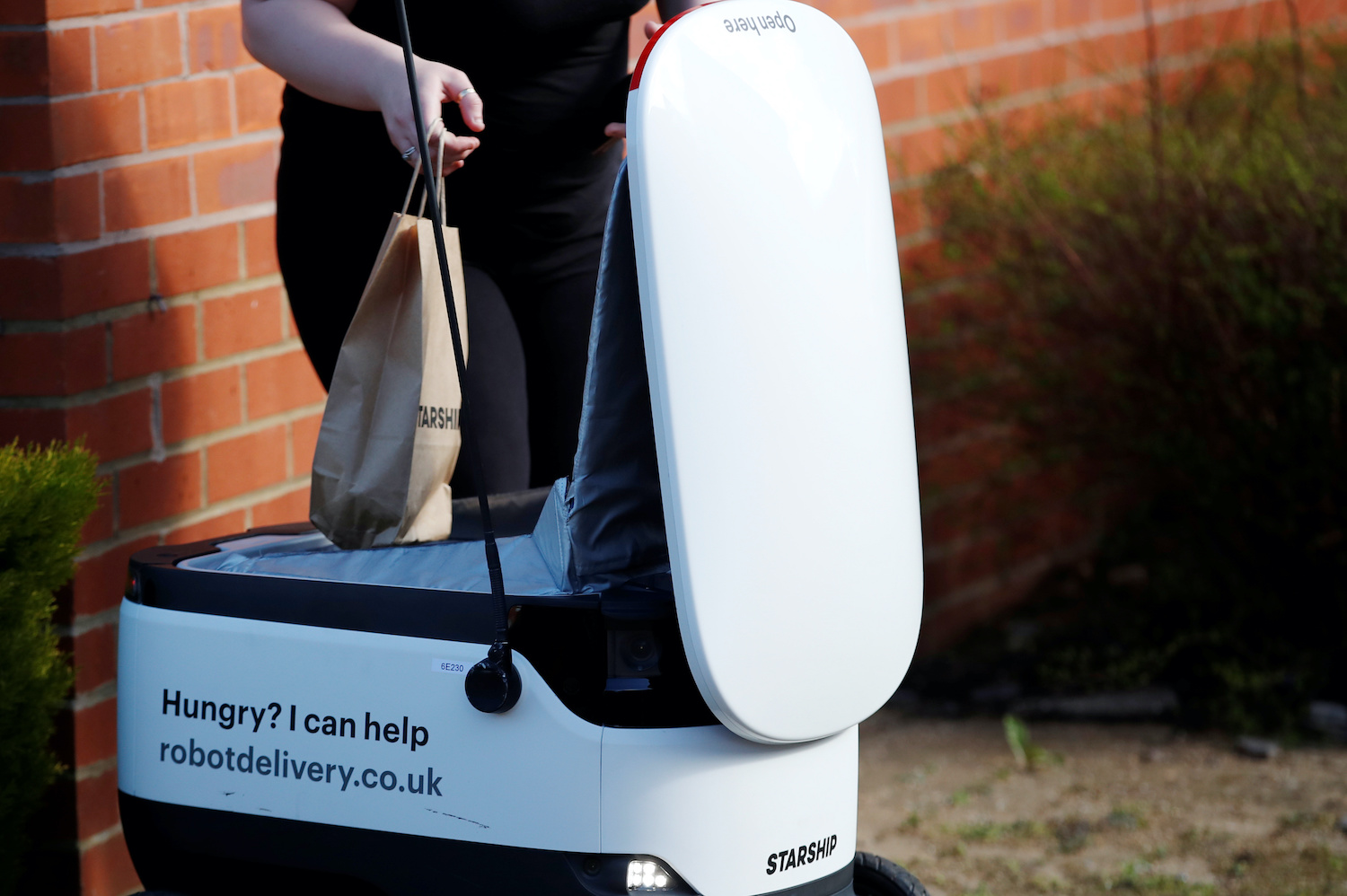 A customer takes a bag from a Starship autonomous delivery robot in Milton Keynes, England. (Photo by Reuters)