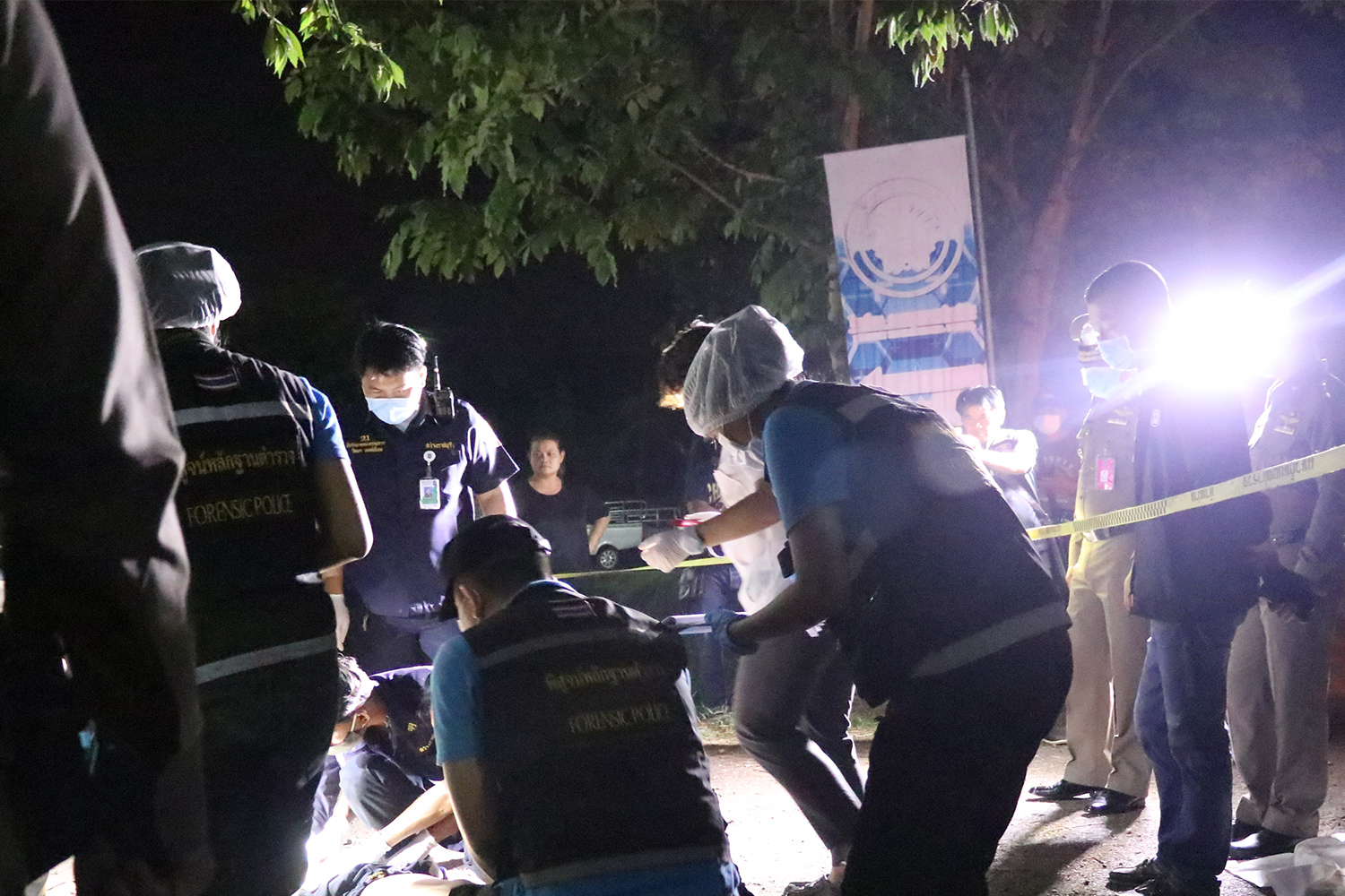 Police inspect the body of one of two people shot to death in Photharam district of Ratchaburi on Saturday night. (Photo by Saichol Srinuanchan)