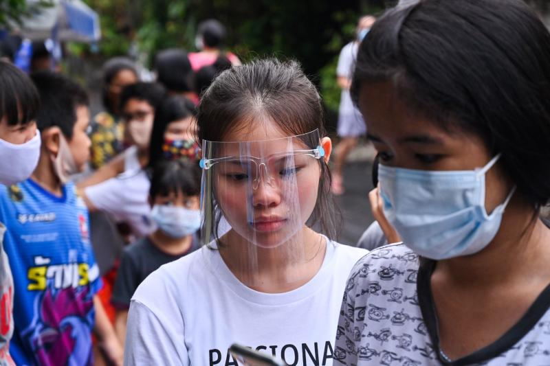 A girl wearing a plastic face shield joins people lining up for food and cash donations from Red Path Party, a political organisation, in Bangkok on Saturday, as Thai citizens are affected by the restrictive measure related to the Covid-19 novel coronavirus. (AFP photo)