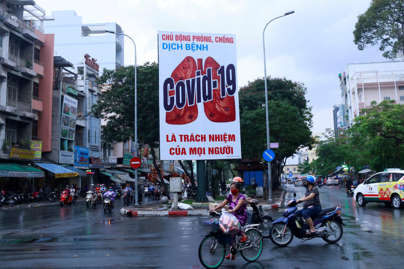 Motorbikes drive past a billboard warning against the coronavirus disease after the government eased nationwide lockdown during the outbreak in Ho Chi Minh, Vietnam, on Saturday. (Reuters photo)