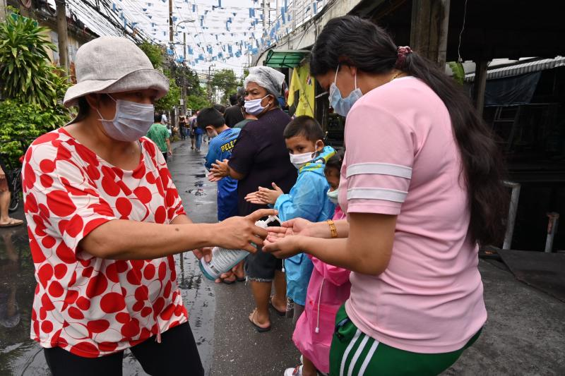 A volunteer disinfects hands of people lining up for food and cash donations from Red Path Party, a Thai political organisation, at a district in Bangkok on Saturday. (AFP photo)