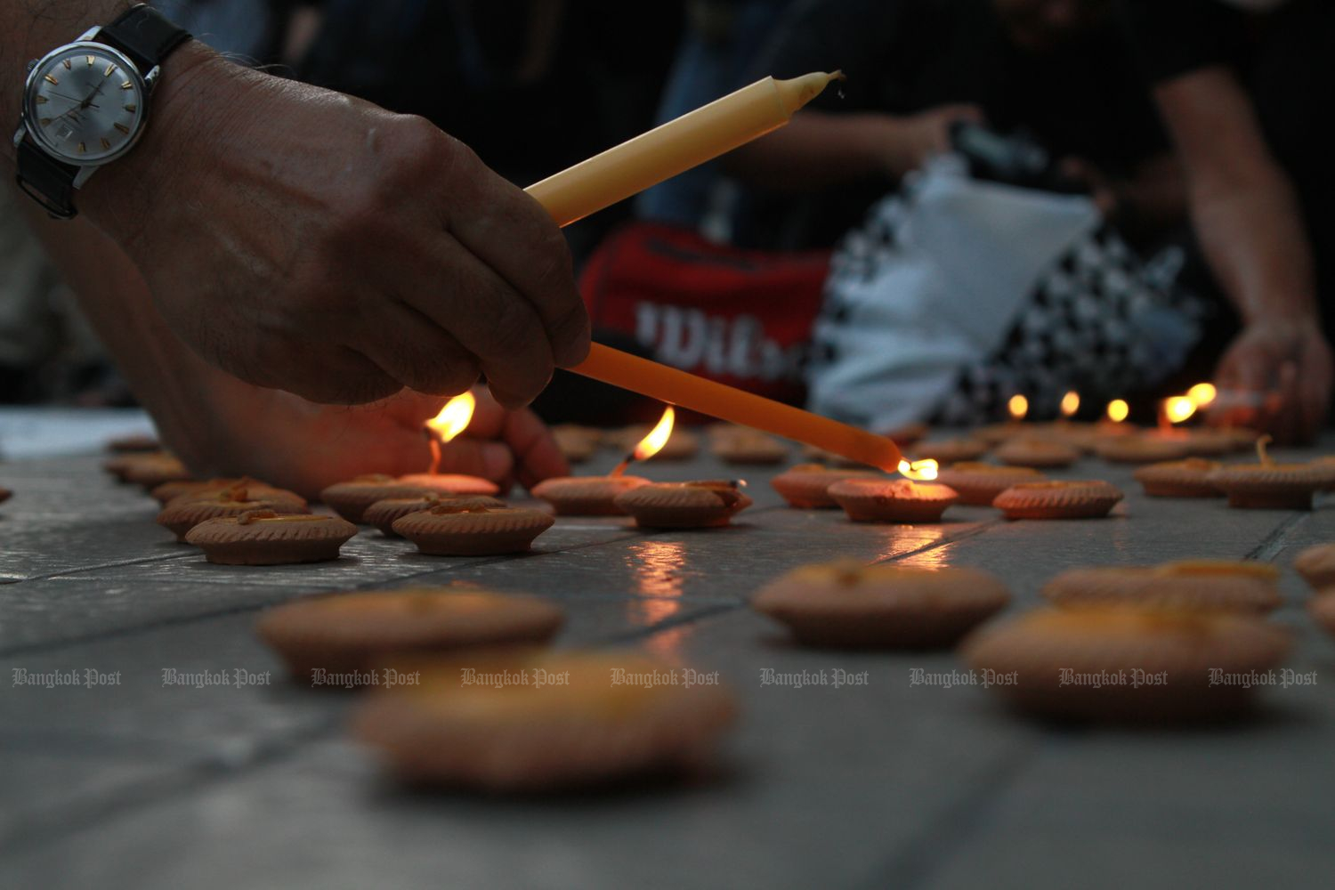 People light candles for the victims of the Feb 8-9 shooting in which 29 people were killed in Nakhon Ratchasima on Feb 13 this year. (Photo by Nutthawat Wicheanbut)