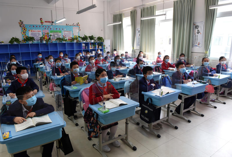 Students wearing face masks sit in a classroom with partitions on their desks as more students in Chongqing return to campus following the coronavirus disease (Covid-19) outbreak, at a school in Chongqing, China on Monday. (Reuters photo)