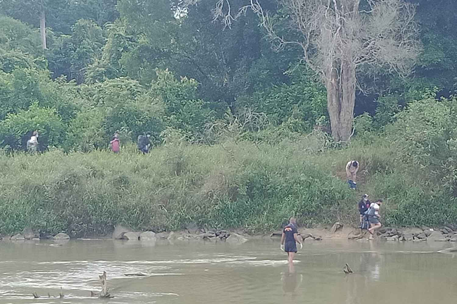 Thai workers wade across the Sungai Kolok river, making an illegal crossing back home to Thailand, in Narathiwat on Wednesday morning. (Photo: Waedao Harai)