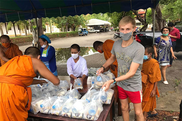 A Russian tourist identified only as Ivan helps monks hand out free meals at Wat Mai Pattararam in Muang district of Surat Thani. (Photo by Supapong Chaolan)