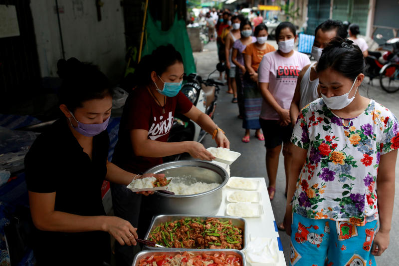 Volunteers give free foods for migrant workers from Myanmar who lost their jobs following the coronavirus disease (Covid-19) outbreak in Bangkok. (Reuters file photo)