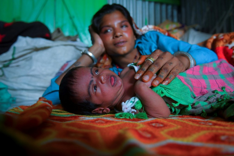 Manju Bauri rests with her newborn baby boy 'Lockdown' in their temporary home in northeast India.