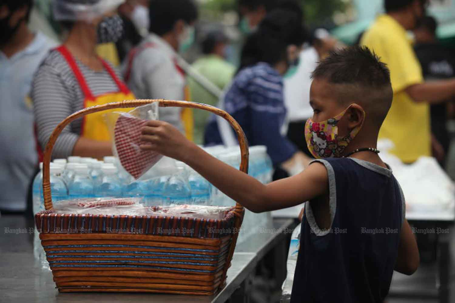 The child picks a face mask from a basketful distributed by the Bangkok Metropolitan Administration in Klong Toey district on Wednesday. (Photo: Arnun Chonmahatrakool)