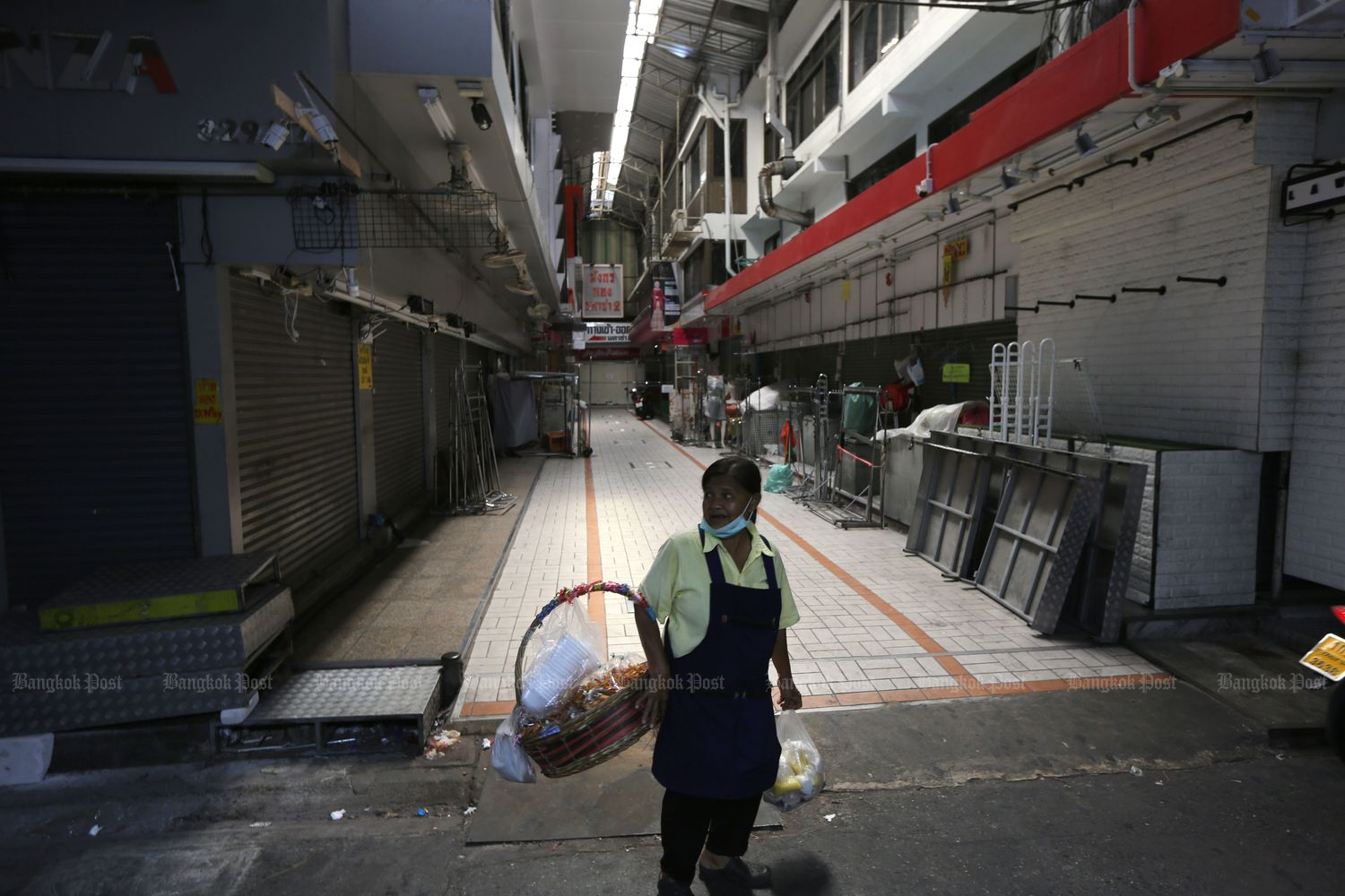 A woman stands before rows of closed shops in Bangkok on March 23. (Photo by Wichan Charoenkiatpakul)