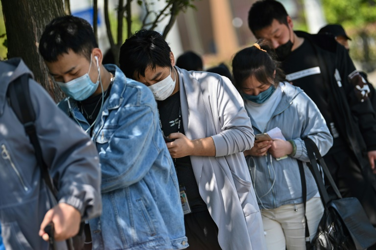Workers wait in line to collect salaries in Shanghai