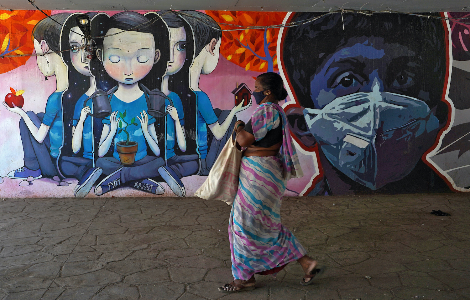 A woman walks past a mural depicting a boy wearing a face mask in Mumbai (Reuters Photo)