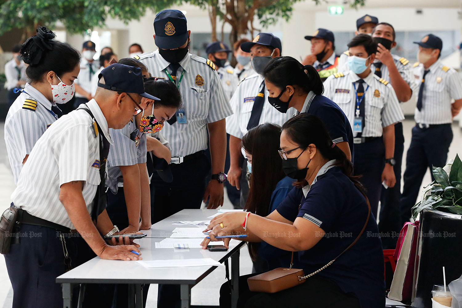 Securing support: More than 250 security guards whose contracts ended on April 30 queue to register with their company's representatives to see what benefits they are entitled to. The guards gathered at the Government Complex building on Chaeng Watthana Road where they had also been working. (Photo by Pronprom Sattabraya)