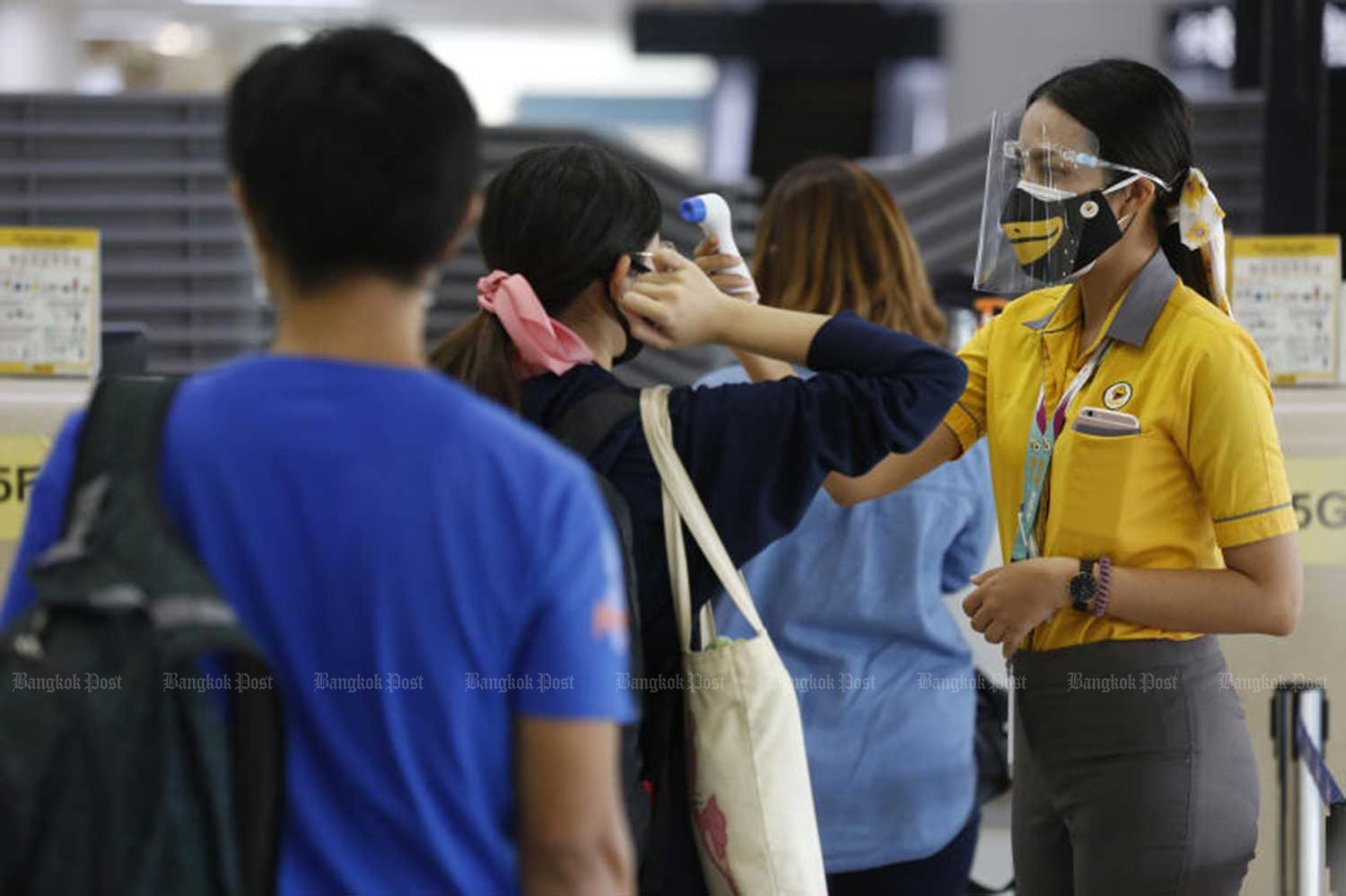 An airline staff member checks the temperature of passengers at Don Mueang airport on Friday, the first day domestic flights resumed. (Photo by Pornprom Satrabhaya)