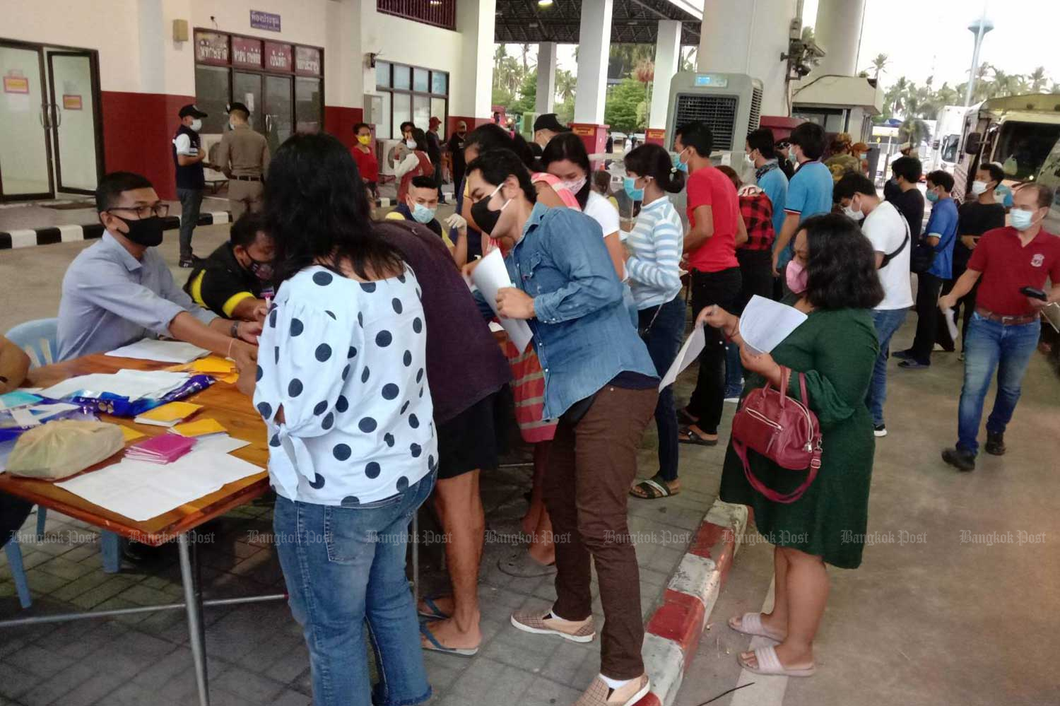 People queue in Phuket to obtain documents that will allow them to pass through the road checkpoint leaving the island. (Photo by Achadtaya Chuenniran)