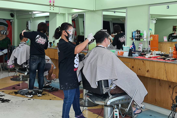 Barbers at Saneh Korn barbershop in Muang district of Nakhon Ratchasima wear face shields and masks as they service customers, after it reopened due to an easing of measures to combat the spread of the coronavirus. (Photo by Prasit Tangprasert)