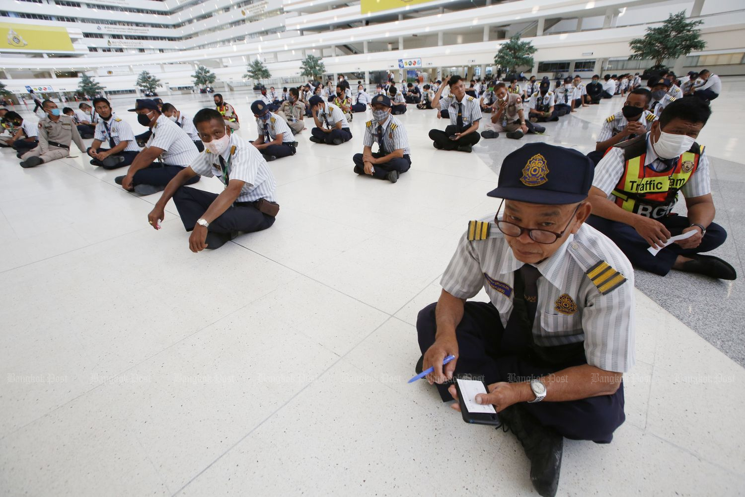 Former employees of a security company contracted to provide the service at the Government Complex gather to seek explanations from the company after the contract ended and they were laid off. They claimed the company still owed them 20,000 baht each in salaries and compensation. (Photo by Pornprom Satrabhaya)