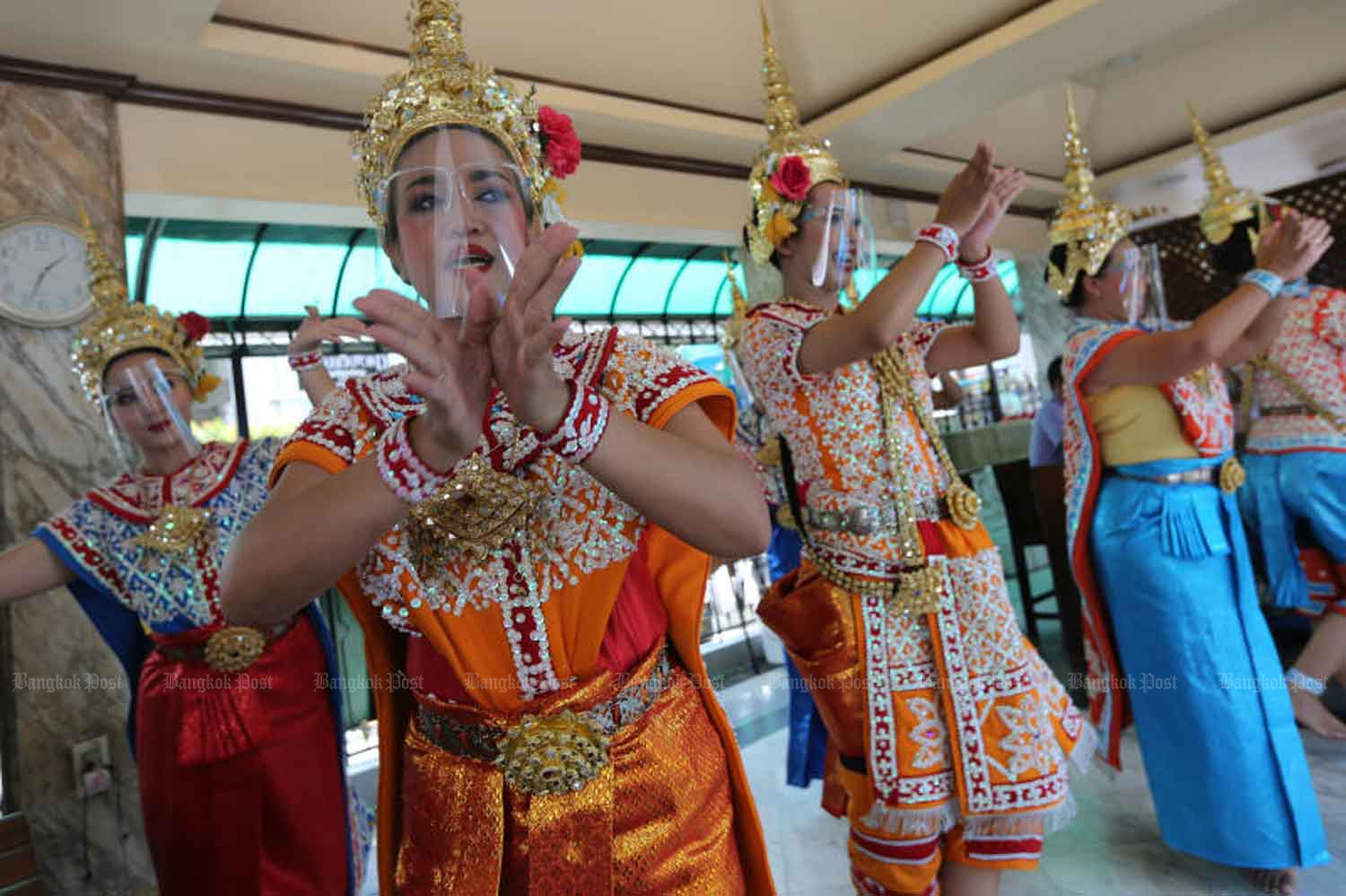 Traditional performers wearing face shields perform a dance at the Erawan Shrine at Ratchaprasong intersection in central Bangkok. The shrine, particularly popular with Chinese tourists, reopened on Friday after it was closed on March 27 at the height of the Covid-19 pandemic. Wichan Charoenkiatpakul